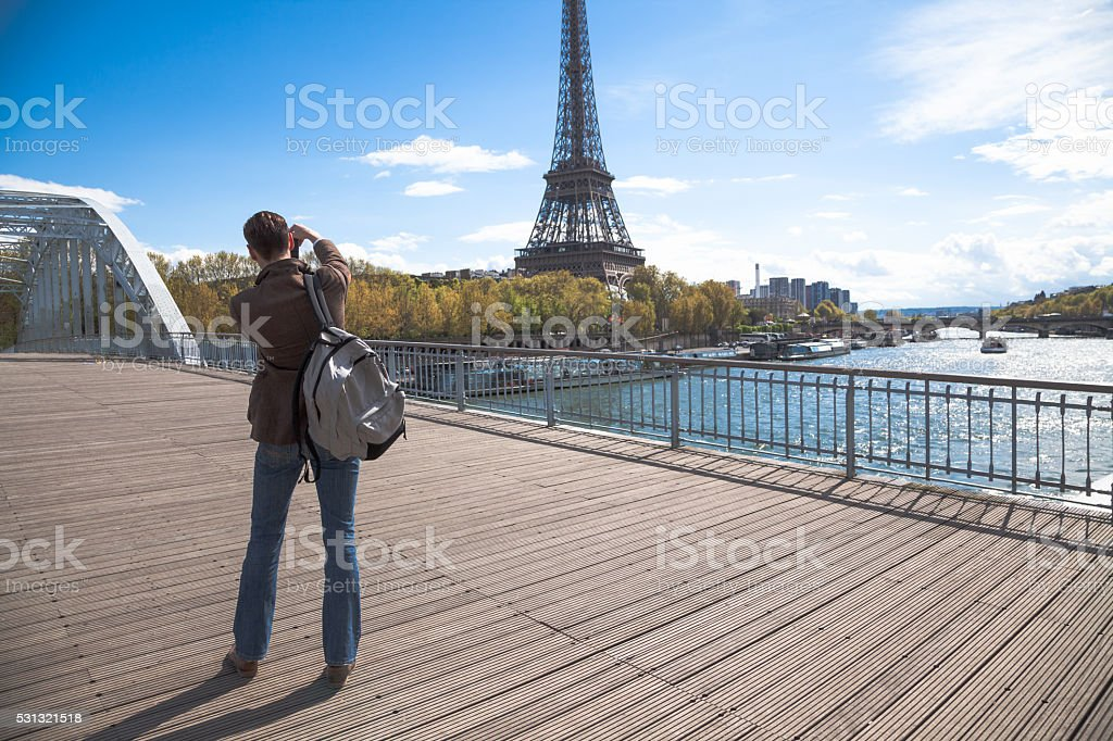 tall young guy photographs sunny Eiffel Tower  in Paris stock photo