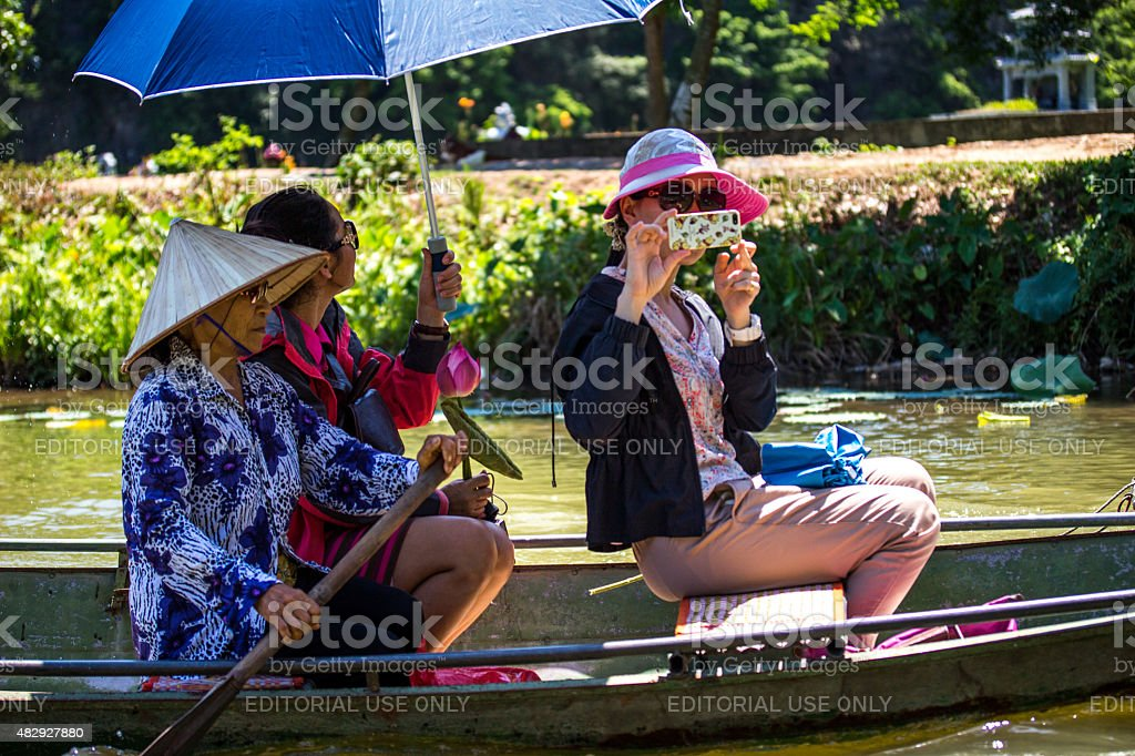 Tam Coc, Vietnam:Tourist on boat taking picture using mobile phone stock photo