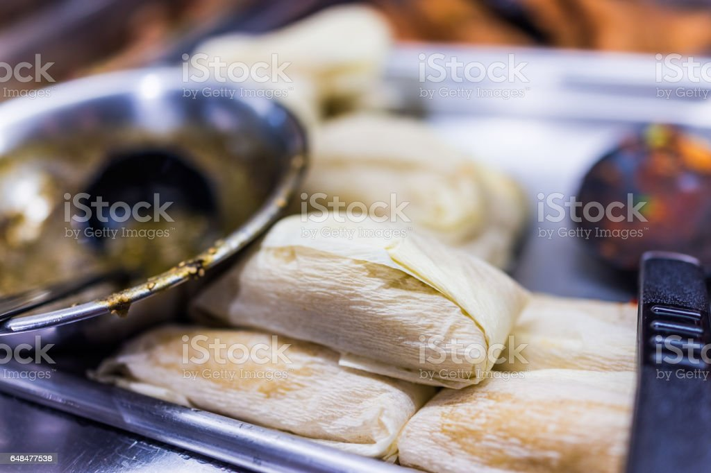 Tamales wrapped in corn husks with sauce on the side stock photo