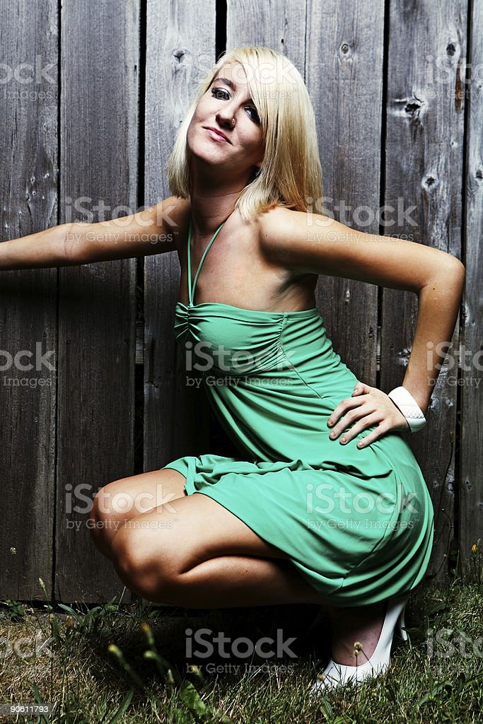 Tan Blonde Girl Posing in Front of a Fence royalty-free stock photo
