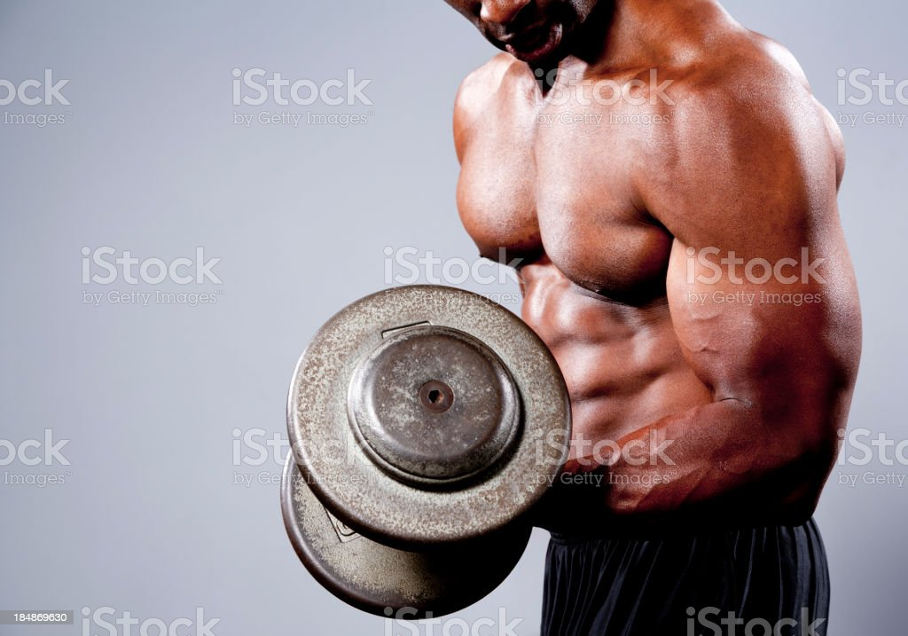 A tan bodybuilder using a heavy barbell royalty-free stock photo
