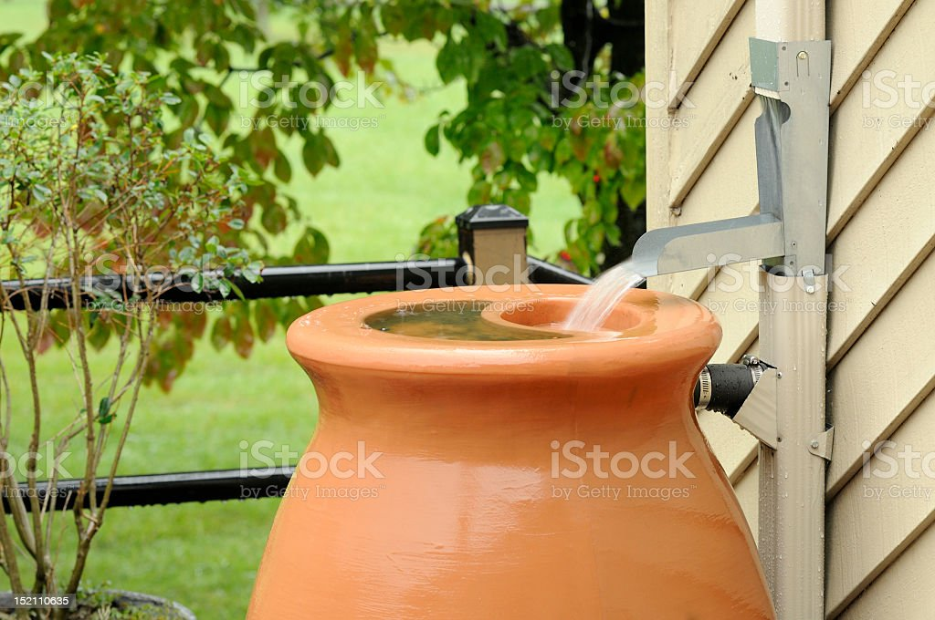 A tan rain barrel outside a home stock photo