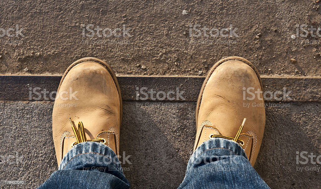 Tan-colored workman's boots up close with blue jeans stock photo