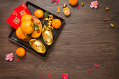 Tangerine oranges and gold 'yuan boa' Chinese new year decorations.