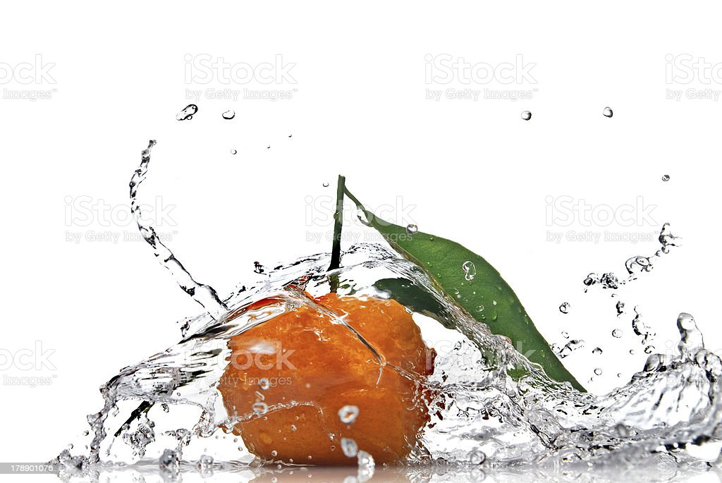 Tangerine with green leaves and water splash isolated on white royalty-free stock photo