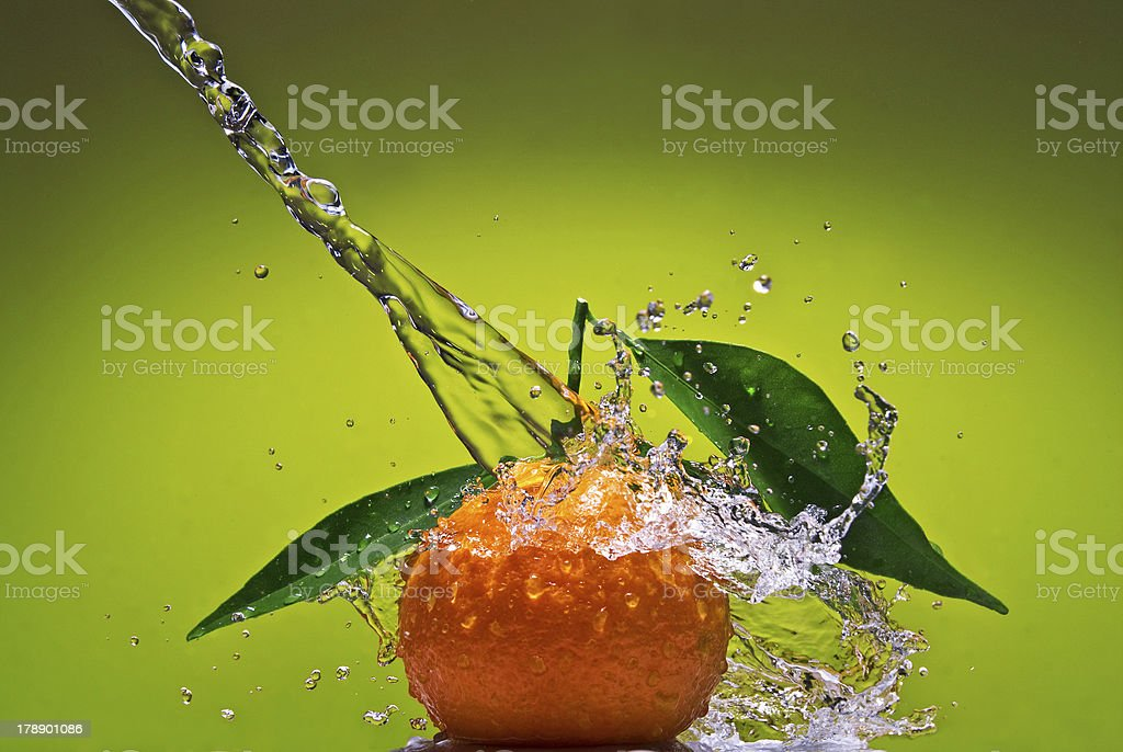 Tangerine with leaves and water splash on green background royalty-free stock photo