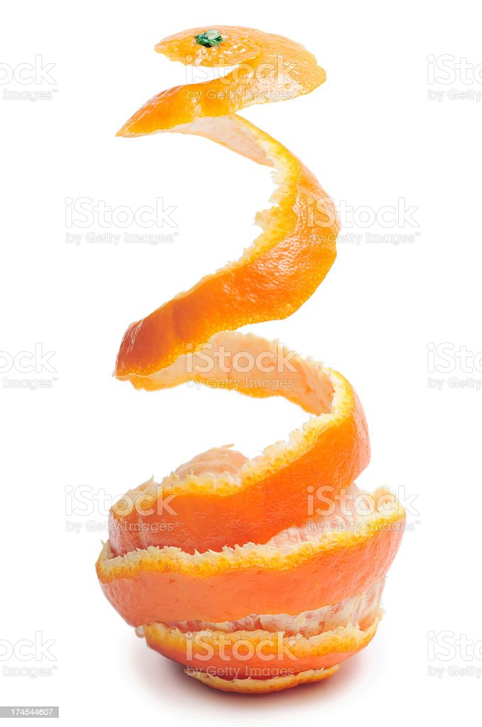 A tangerine with the peel being taken off of in mid air stock photo