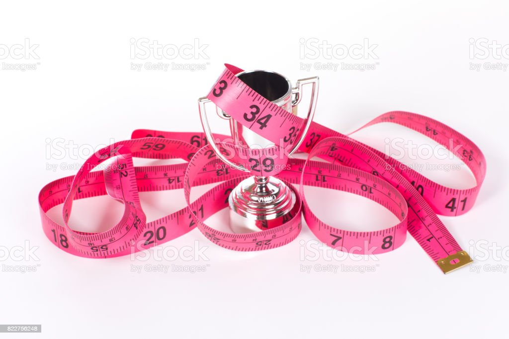 Tangled measuring tape around sports cup stock photo