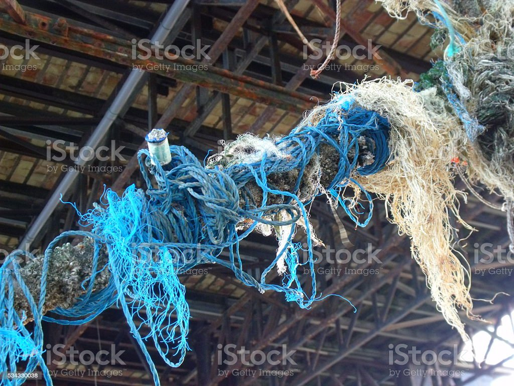 Tangled ropes under a pier stock photo