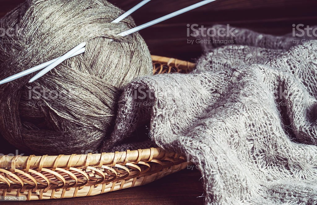 tangles of of woolen yarn and knitting needles in a basket stock photo