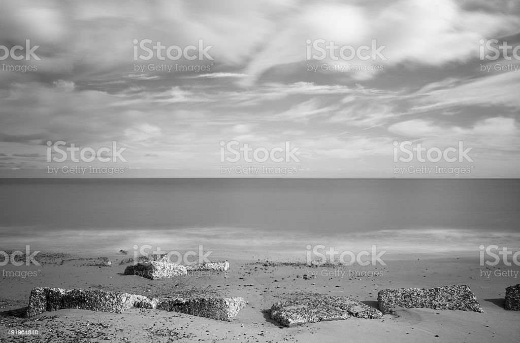 Tank traps on Sizewell beach, long exposure monochrome stock photo