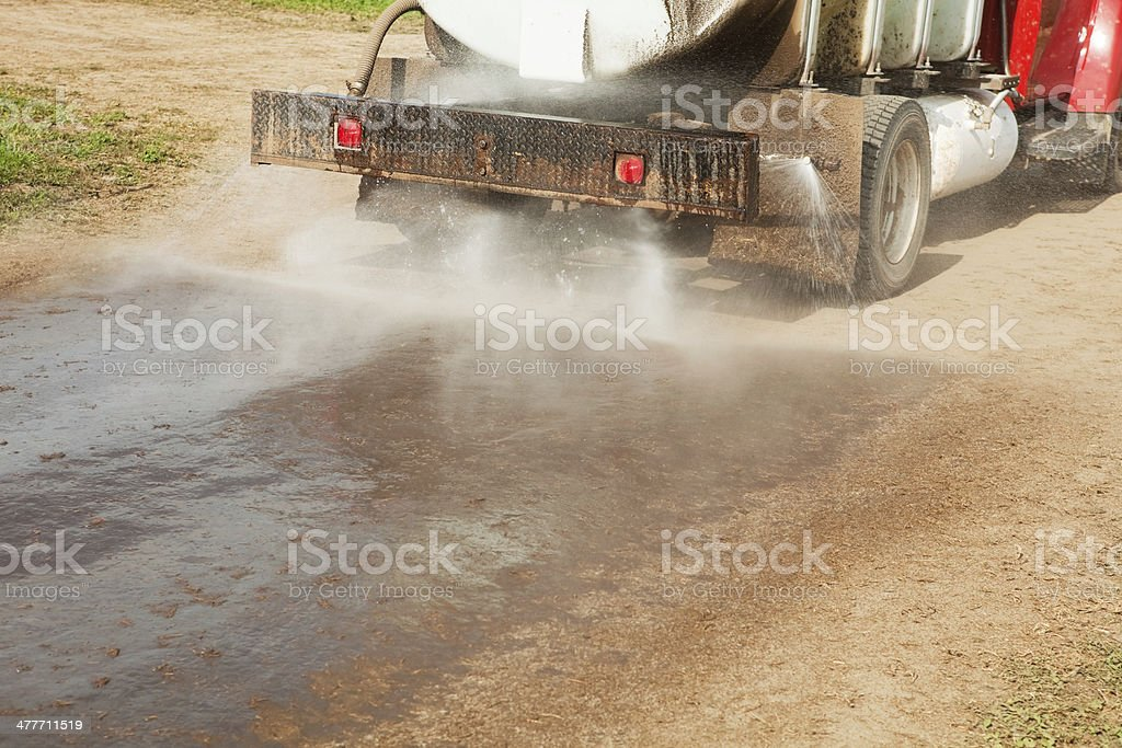Tank Truck Spraying Water on Dirt Road to Control Dust stock photo