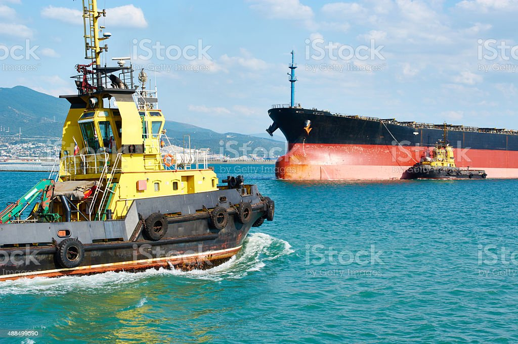 Tanker barge and powerful tugboats in sea stock photo