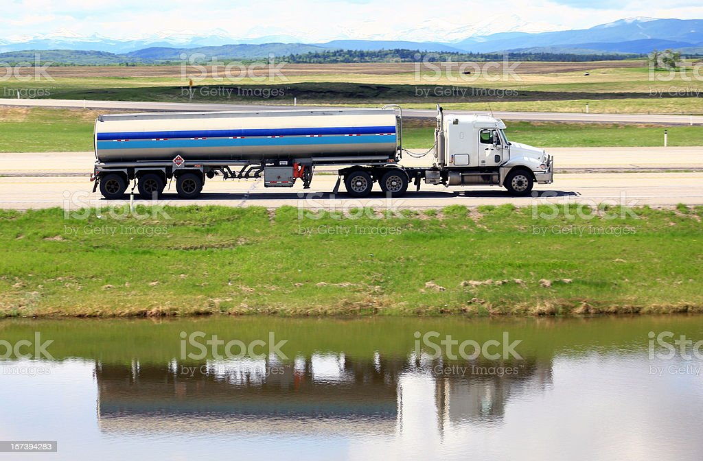 Tanker Semi-Truck on a Freeway with Mountains stock photo