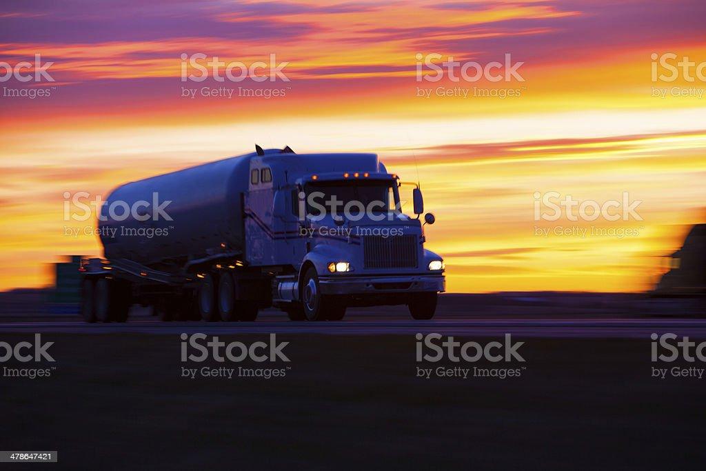 Tanker truck speeding along a highway at sunset. stock photo