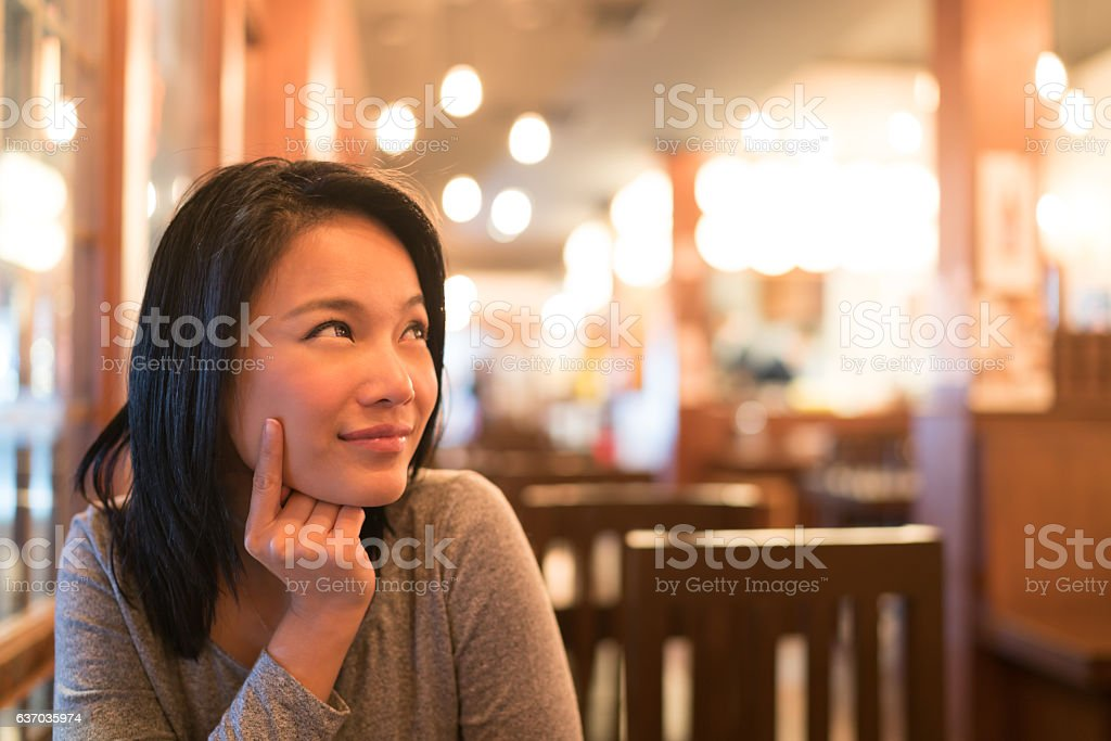 Tanned Asian girl looking upward to copy space at restaurant stock photo