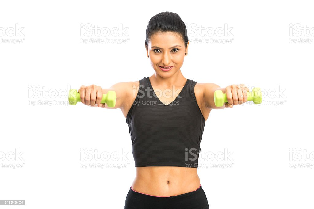 tanned girl in a sportswear doing exercises with dumbbells stock photo