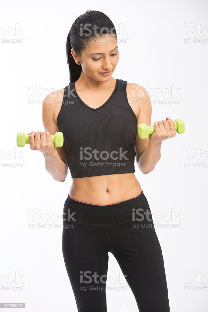 tanned young girl in a sportswear doing exercises with dumbbells stock photo