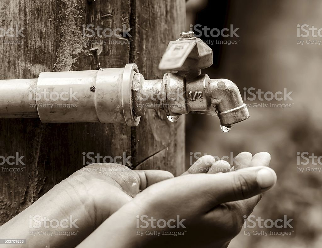 Tap water dropped on hands. stock photo