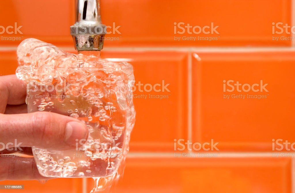 Tap water overflowing into a small glass royalty-free stock photo
