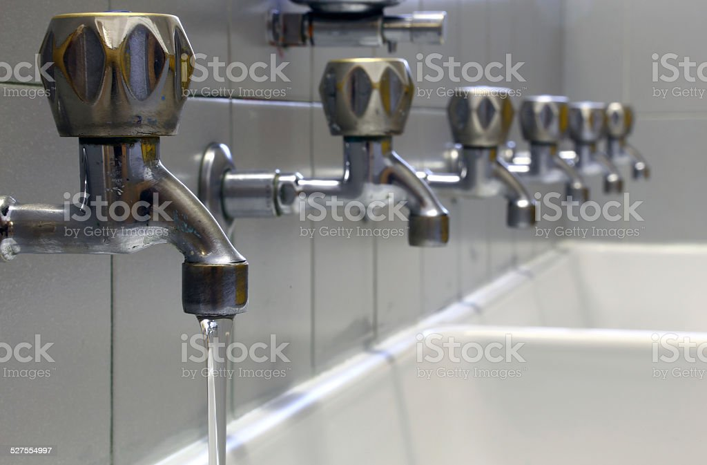 tap with water and many taps shut stock photo