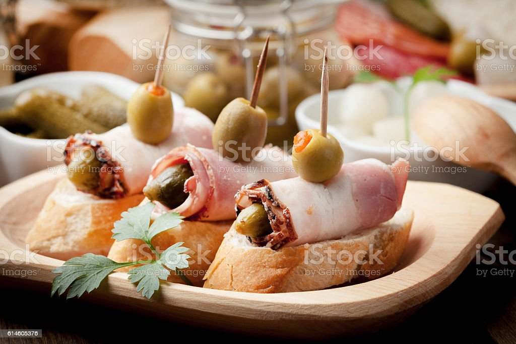 Tapas with sliced bacon, olives and cucumber. stock photo