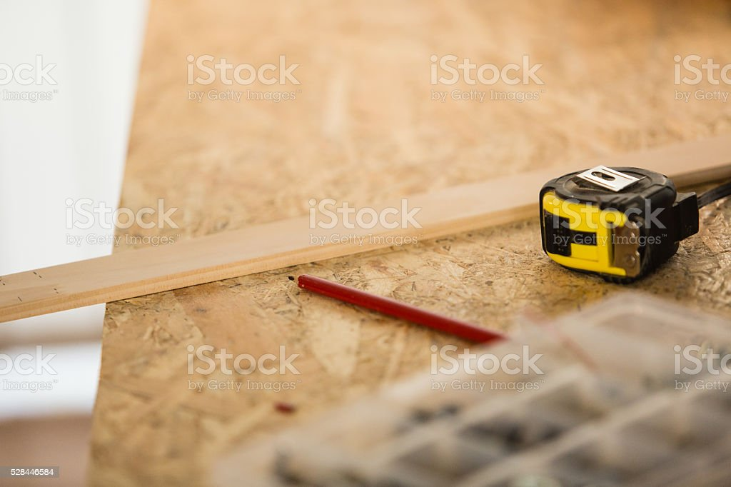 Tape measure and pencil next to the wooden plank stock photo