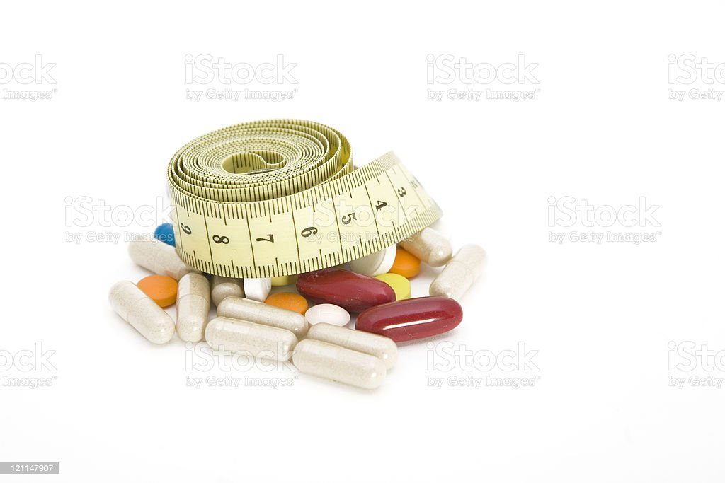 Tape measure and pills royalty-free stock photo