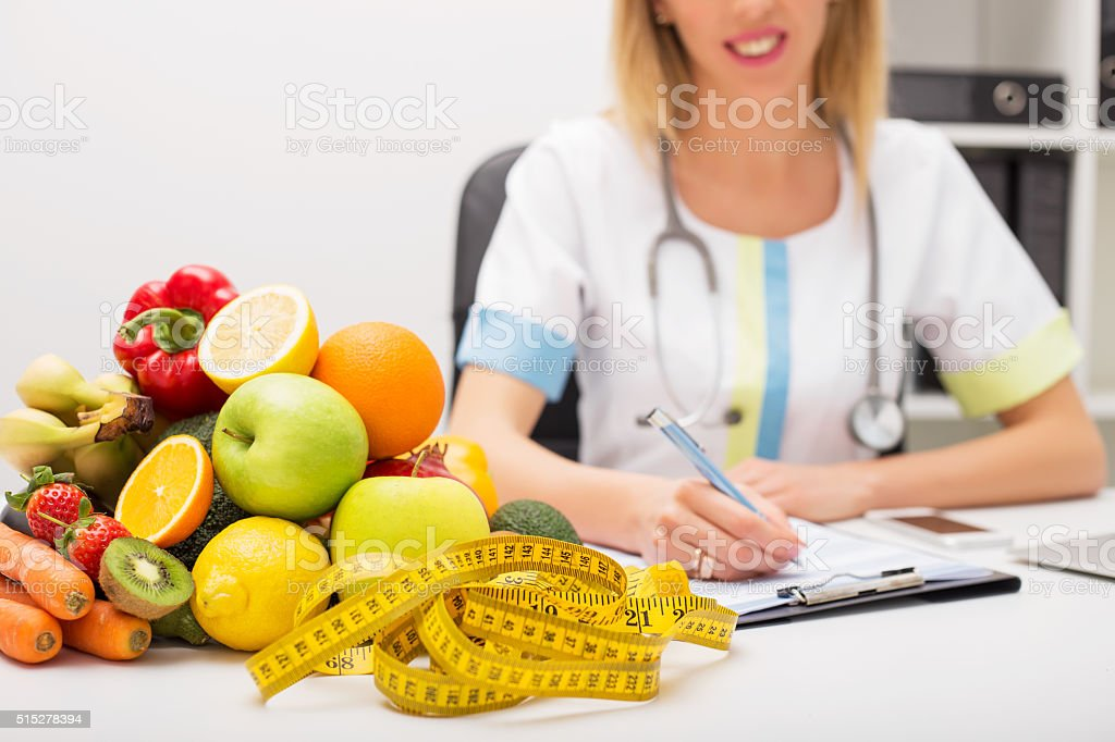 Tape measure and vegetables on doctors table stock photo