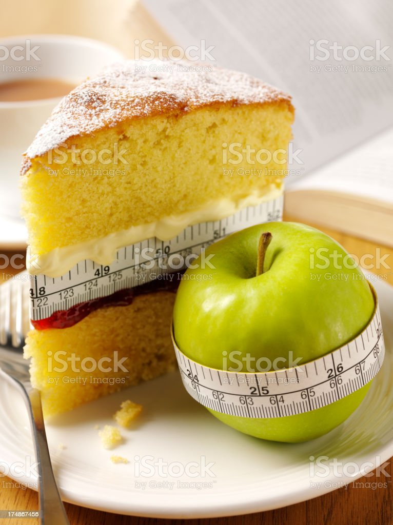 Tape Measure Around a Sponge Cake and Apple stock photo