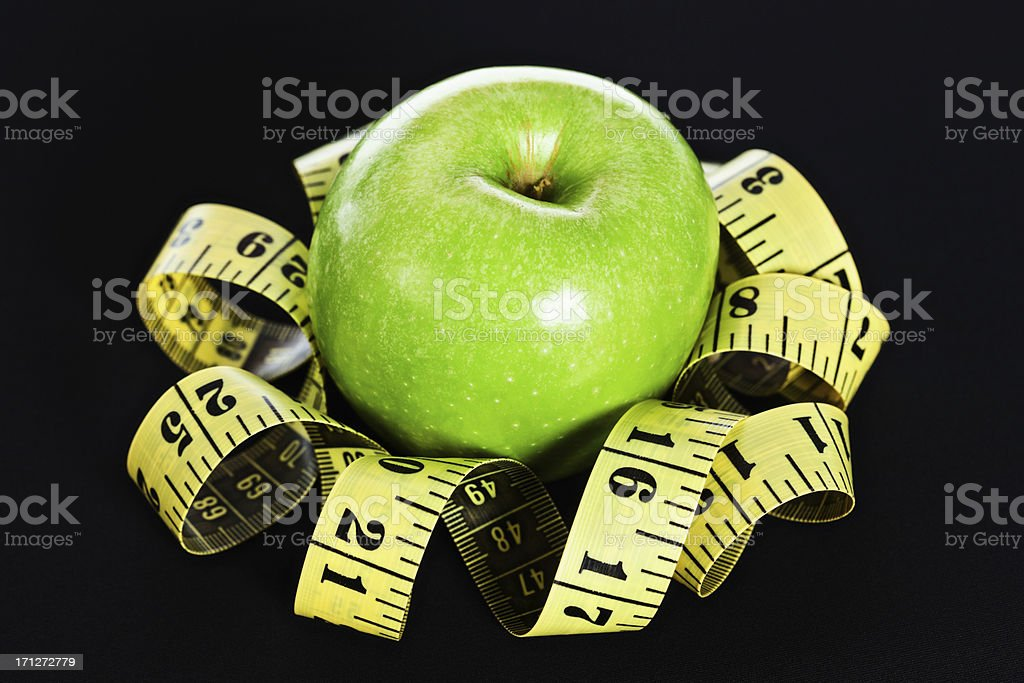 Tape measure arranged round apple like a flower stock photo