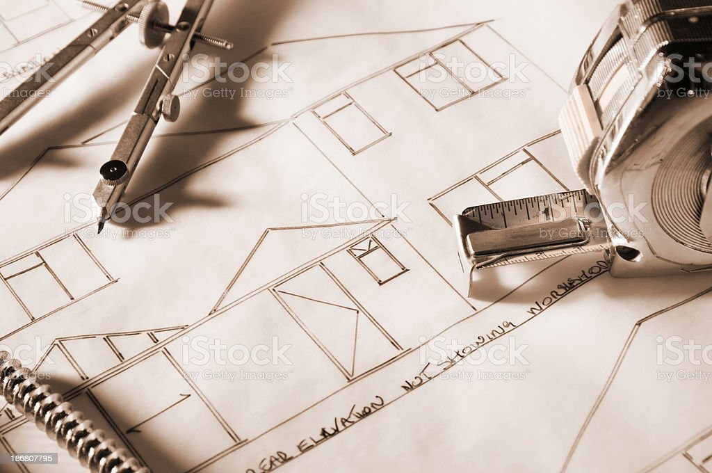 Tape measure, compass and bolts on house blueprints royalty-free stock photo