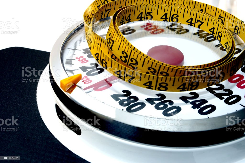 Tape measure laying on a scale stock photo