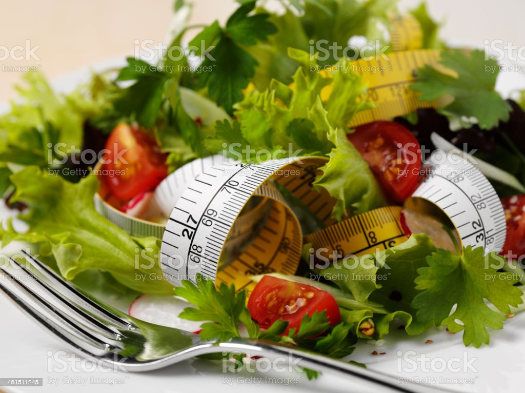 Tape Measure Mixed with a Tomato and Lettuce Salad stock photo