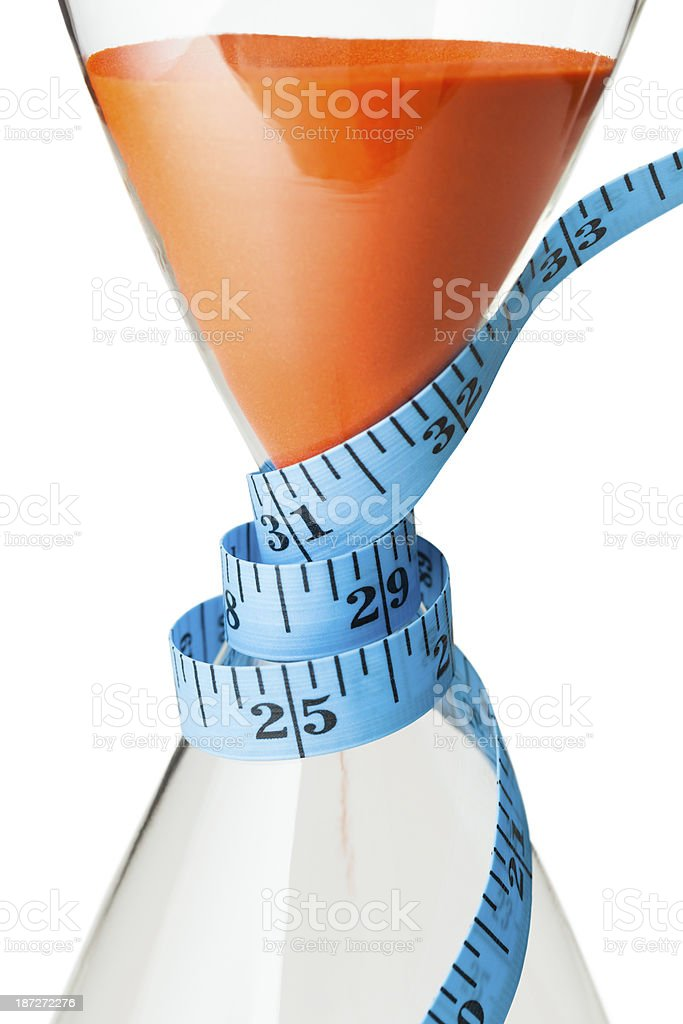 Tape measure wrapped around an hourglass royalty-free stock photo