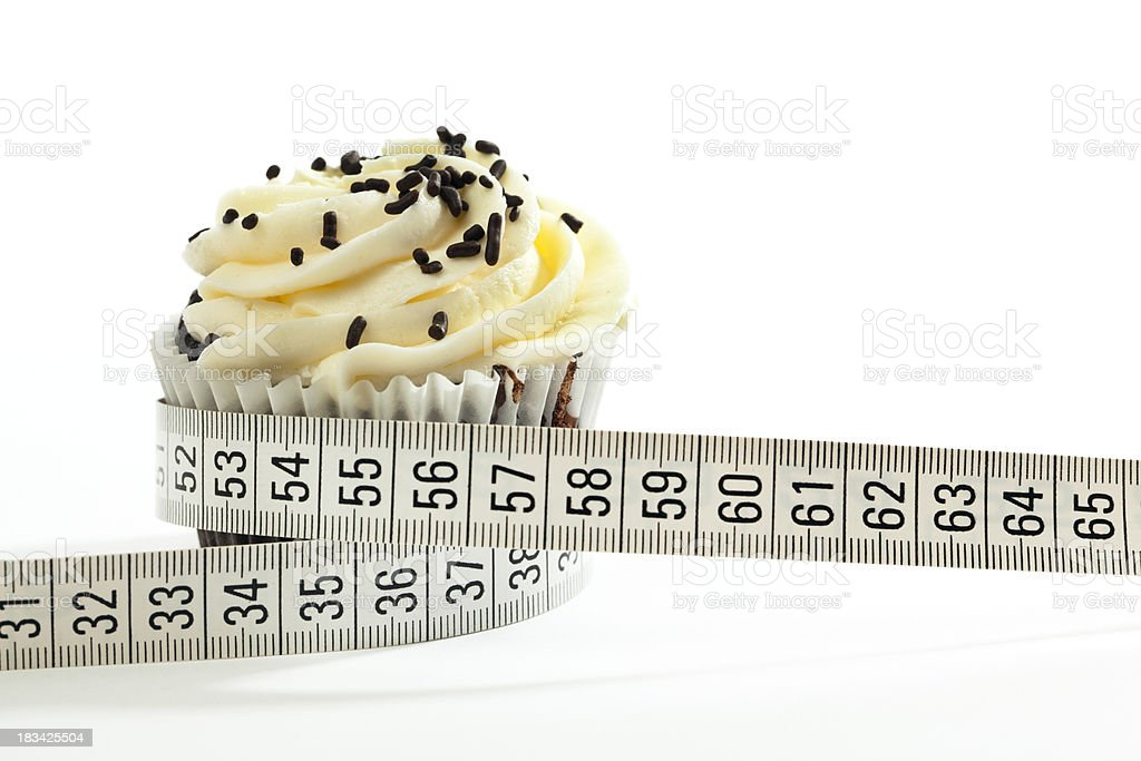 Tape Measure Wrapping Cupcake per Unhealthy Eating, Weight Control Metric royalty-free stock photo