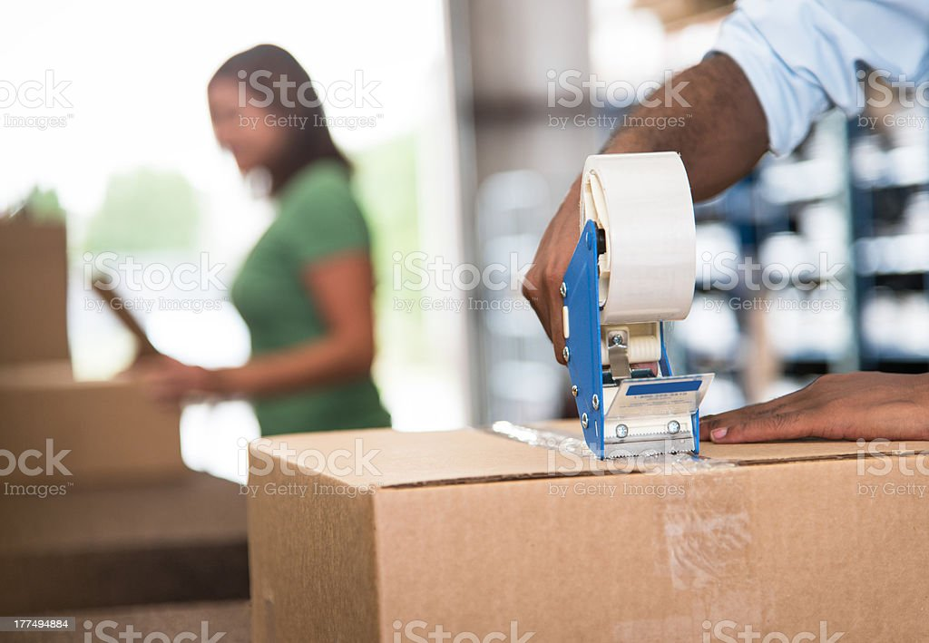 Taping boxes in a warehouse stock photo