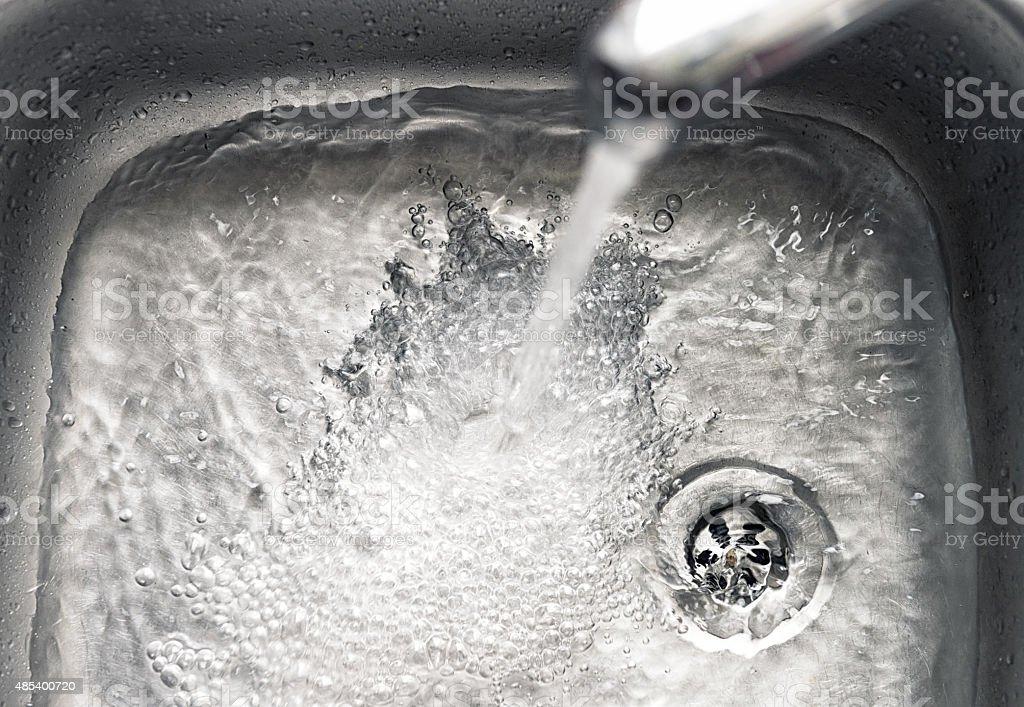 Tapwater running down the drain stock photo
