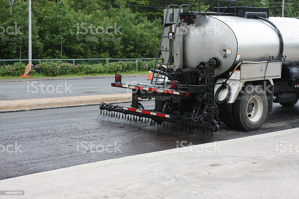 A tar truck tarring a road for construction stock photo