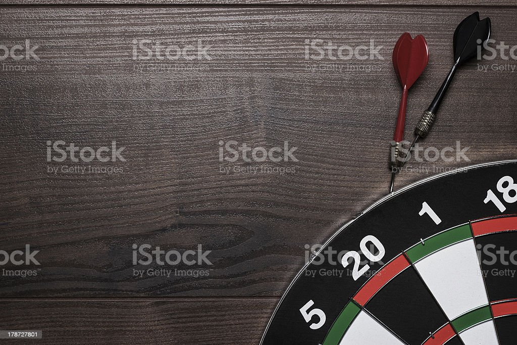 target and two darts over brown wooden table background stock photo