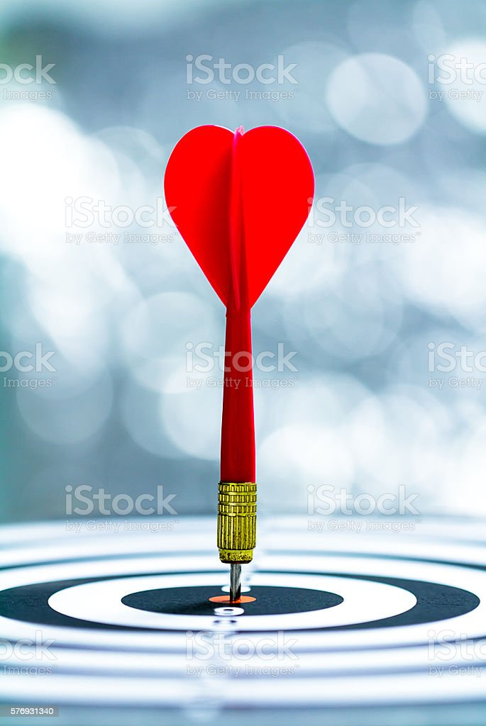 target dart with arrow over blurred bokeh background stock photo