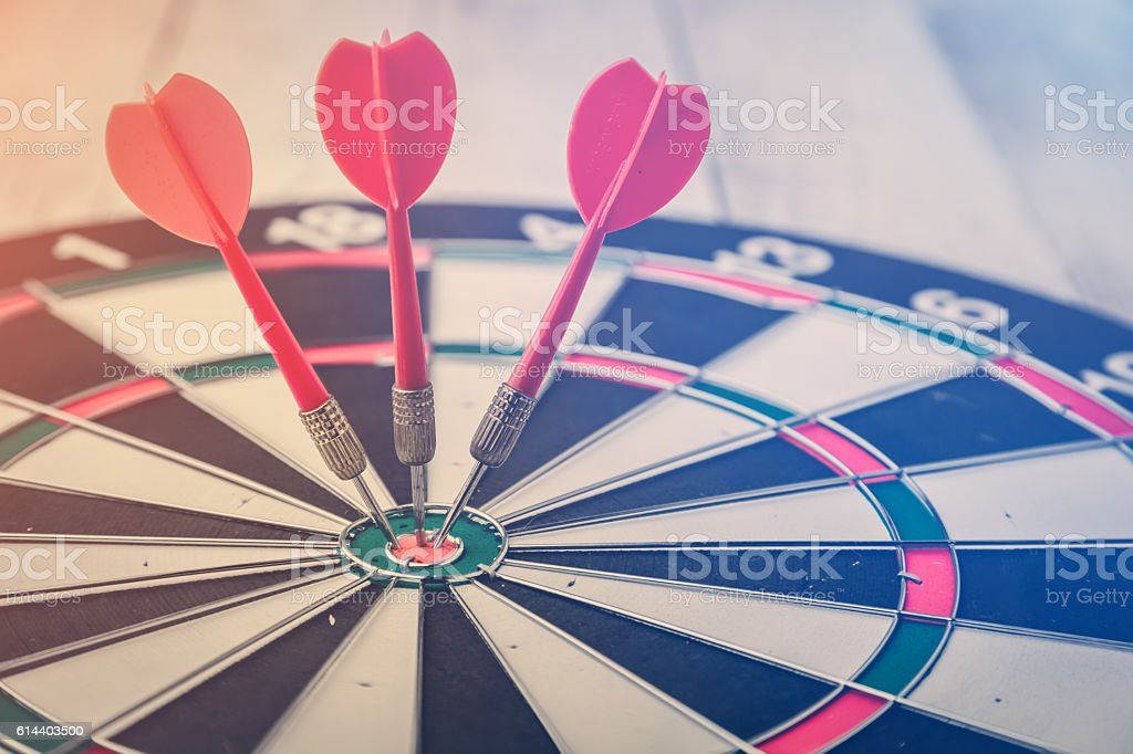 target dart with arrow over white wood background stock photo