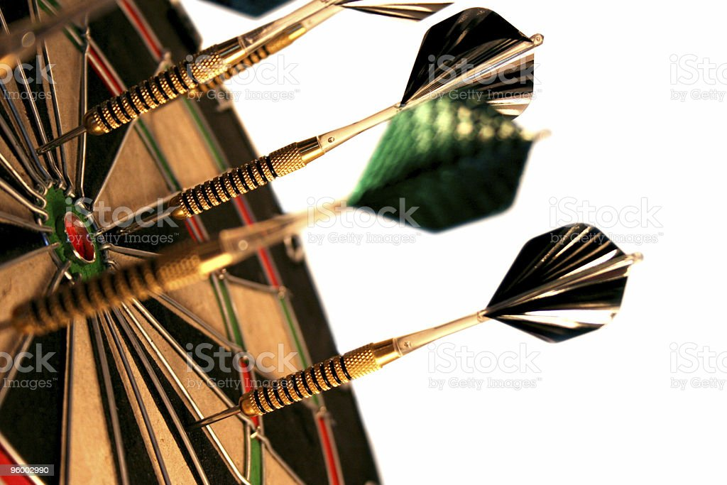 Target practice with feathered darts on a dartboard royalty-free stock photo