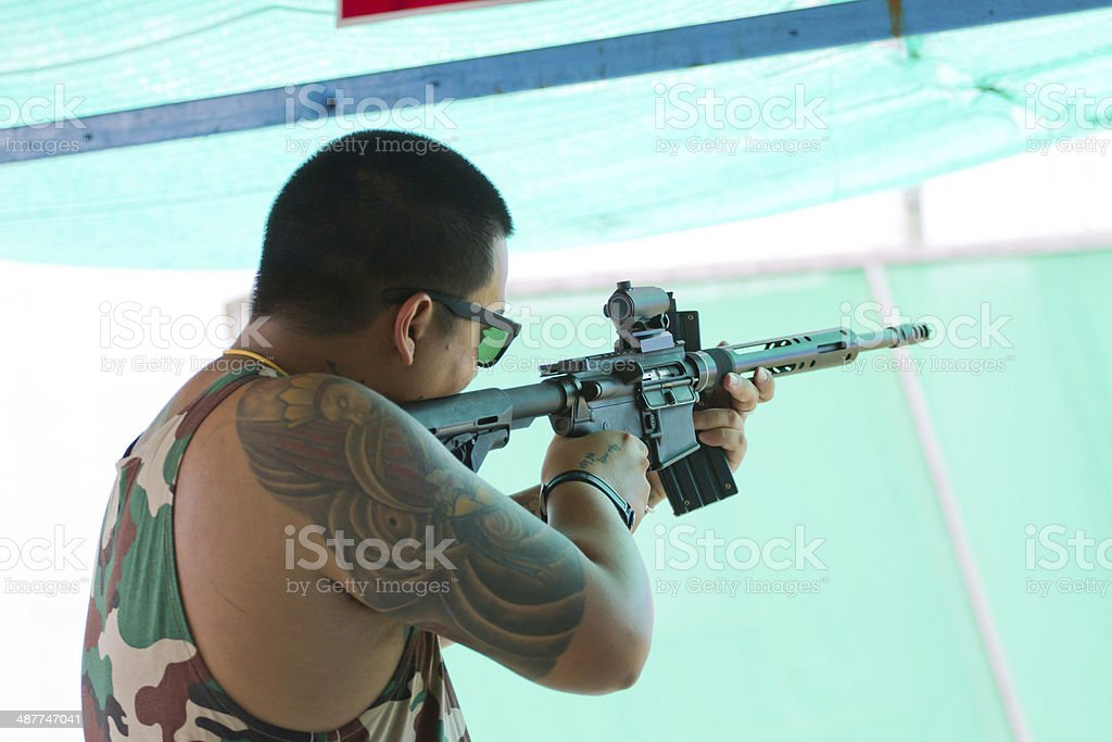 Target practicing with gun In the shooting range stock photo