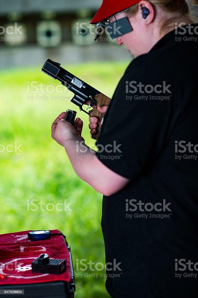 Target shooting, loading the pistol stock photo