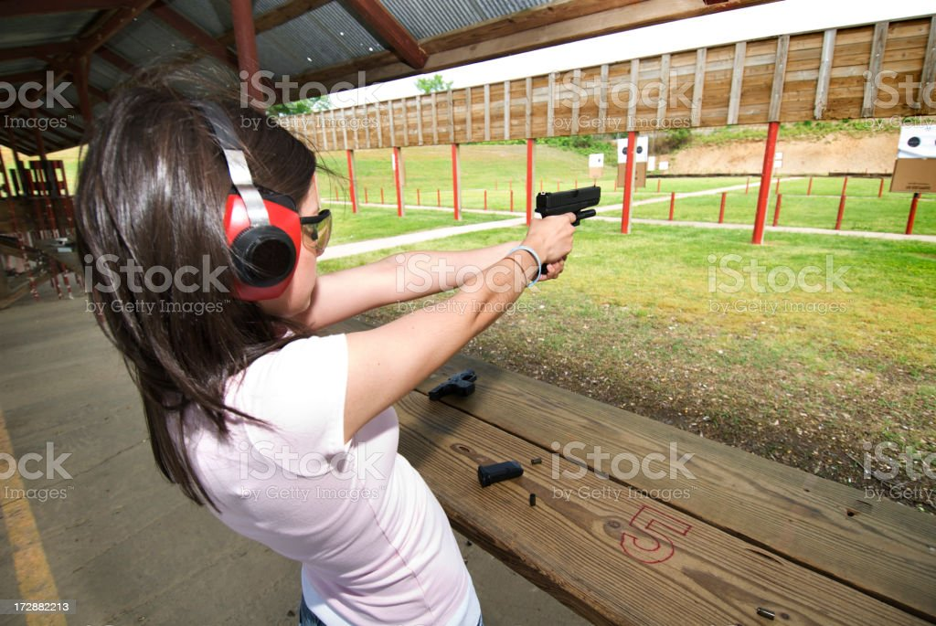 \'Young woman practices her pistol skills at an outdoor shooting...