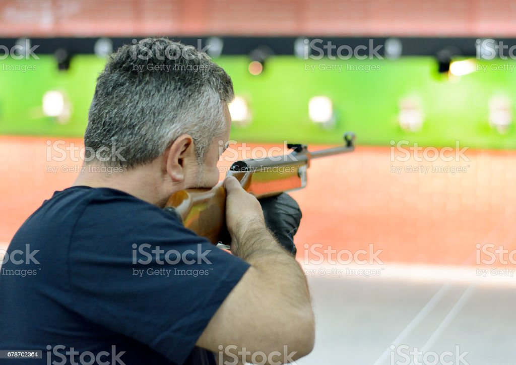 Man targeting with airgun on competition. Air rifle and targets.