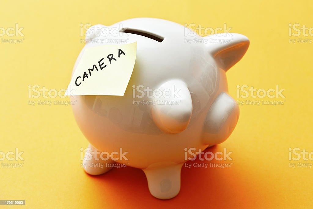 Targeted saving: piggybank with label saying CAMERA royalty-free stock photo