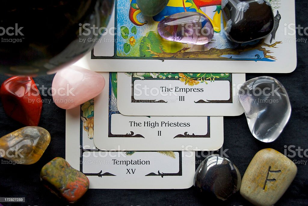 Tarot card reading with gems scattered on the table stock photo