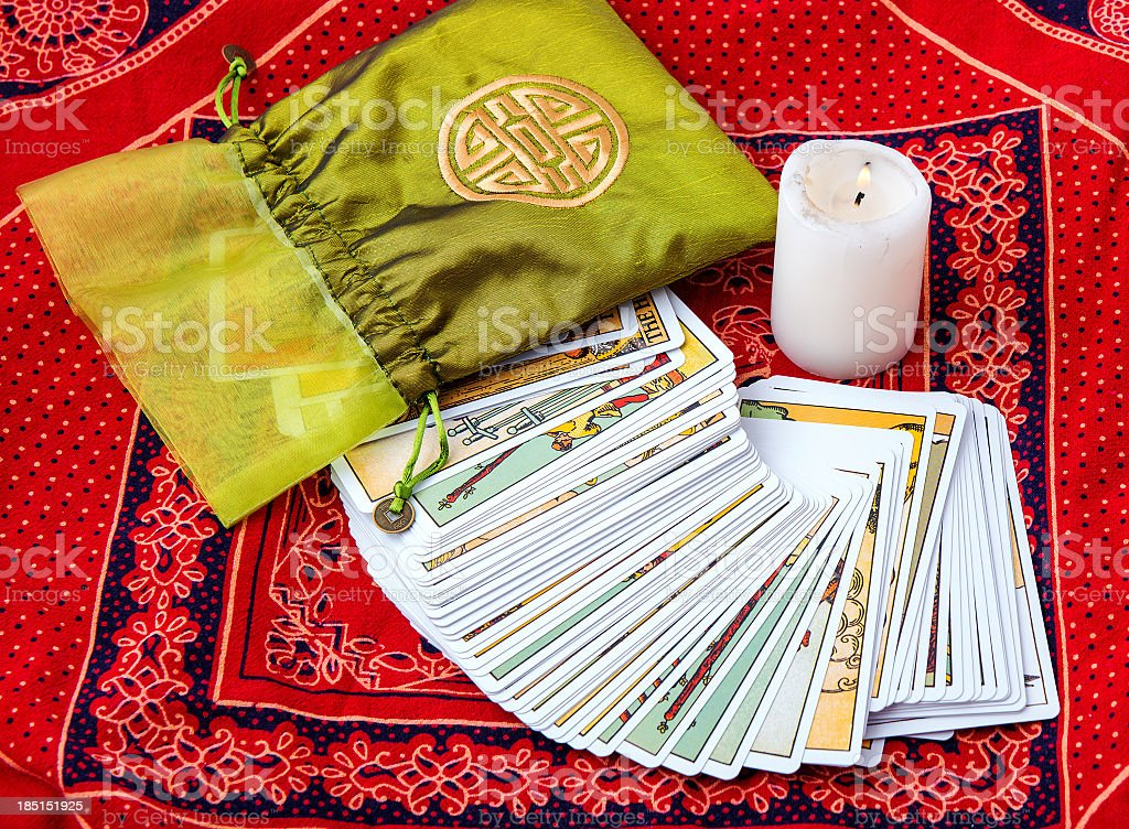 Tarot cards fanned out on a red cloth and a burning candle stock photo